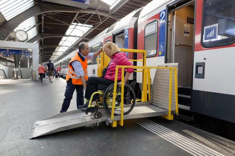 Un employé des CFF aide une personne en chaise roulante à grimper dans le train. [Gaëtan Bally - Keystone]