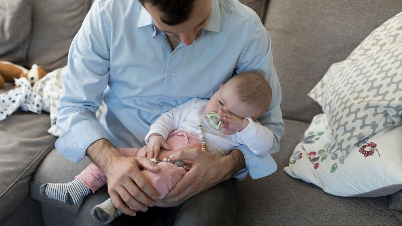 Un père est assis sur un canapé avec son bébé dans les bras. [Gaëtan Bally - Keystone]