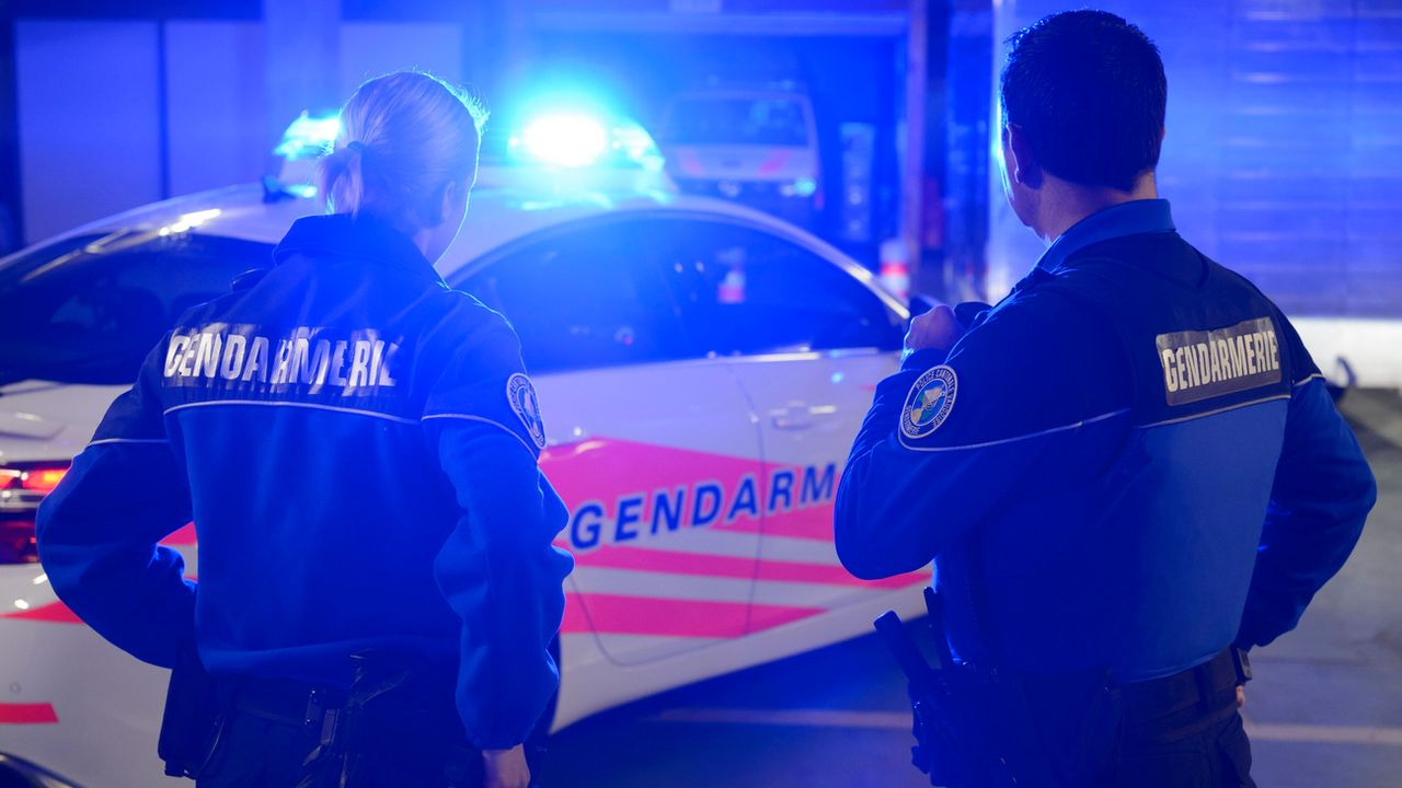 Deux gendarmes vaudois devant leur voiture de patrouille. [Laurent Gilliéron - Keystone]