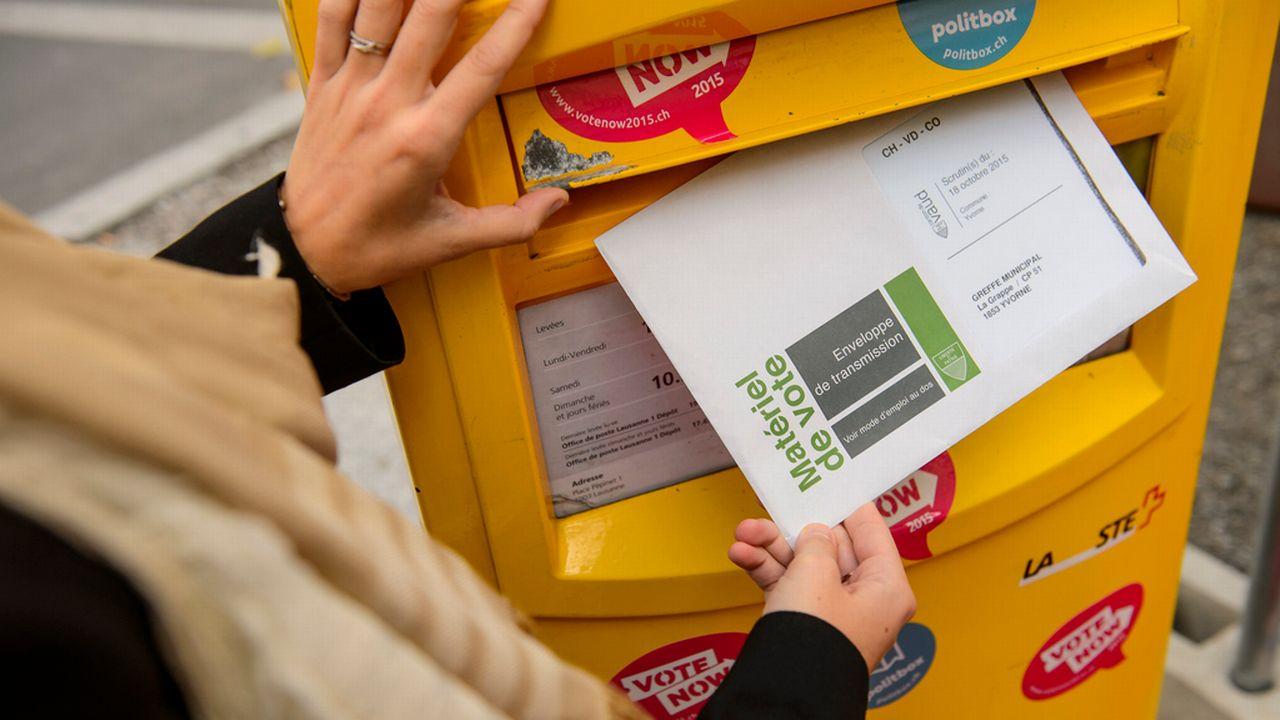 """Une personne glisse un bulletin de vote dans une boite aux lettres lors de l'opération """"Easyvote"""" pour inciter les jeunes à voter en 2015. [Jean-Christophe Bott - Keystone]"""