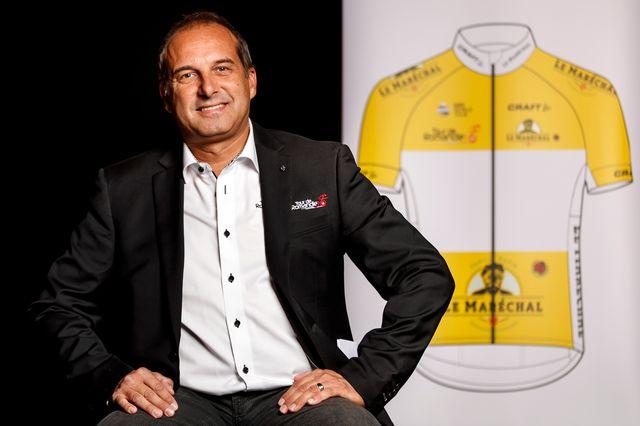 Richard Chassot, directeur du Tour de Romandie, devant le nouveau maillot sponsorisé par Le Maréchal. [Valentin Flauraud - Keystone]