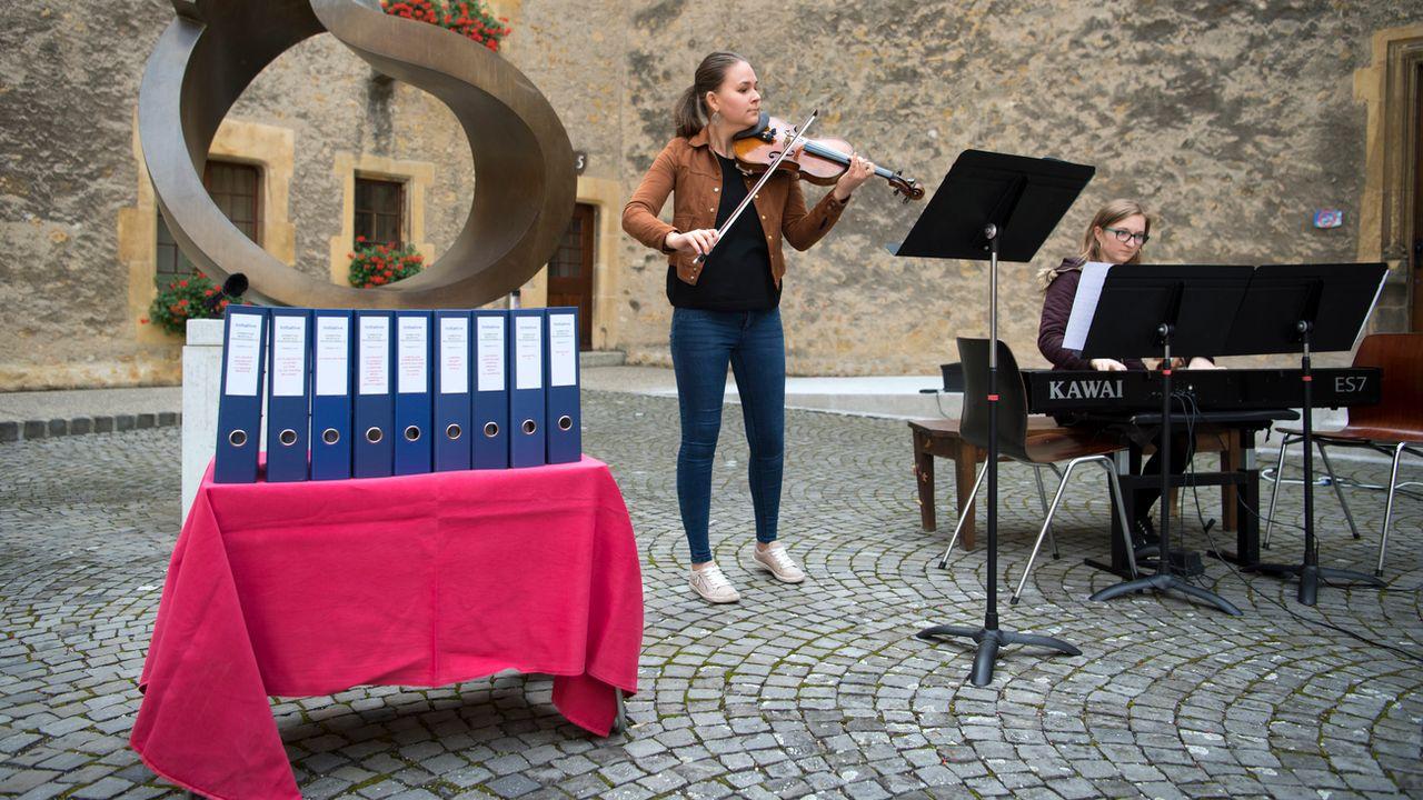 Deux élèves de la Haute école de musique de Neuchâtel et les classeurs contenant les signatures de l'initiative.  [Laurent Gillieron - Keystone]