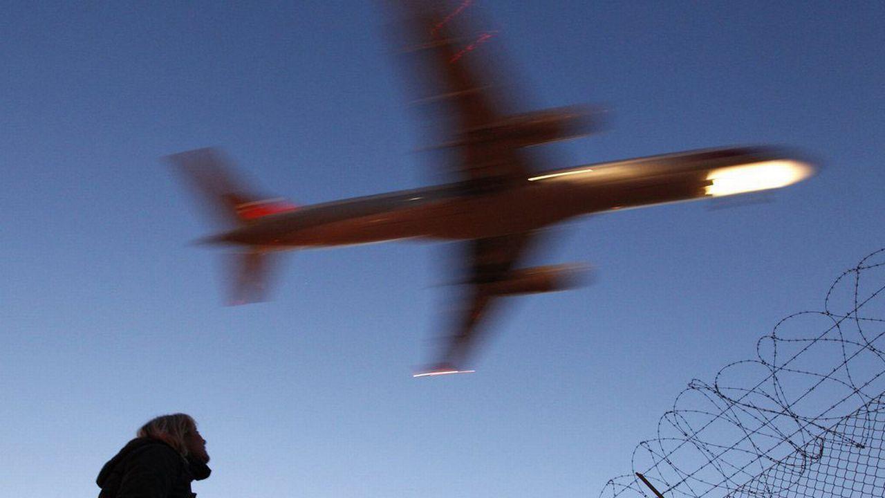 Une femme regarde un avion au-dessus de l'aéroport de Genève. [Peter Klaunzer - Keystone]