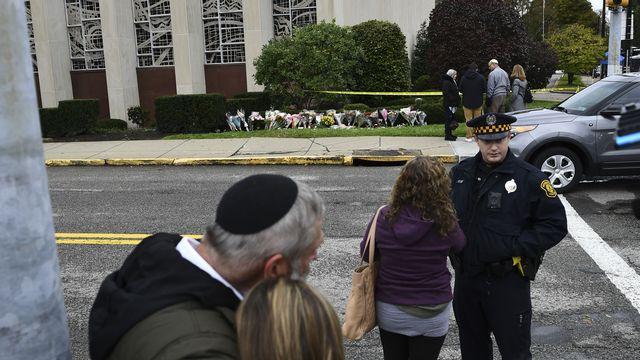 Des personnes rassemblées le 28 octobre devant le mémorial installé à l'extérieur de la synagogue où s'est produite la fusillade. [Brendan Smialowski - AFP]
