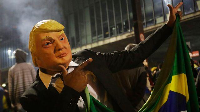 Un partisan de Bolsonaro célèbre la victoire de son candidat à la présidentielle au Brésil en portant un masque du président américain Donald Trump. [AP Photo/Nelson Antoine - Keystone]