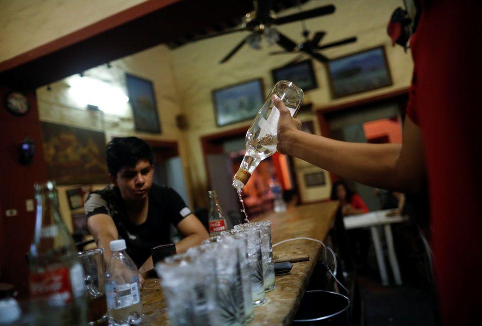 Un résident regarde un barman préparer des verres à base de tequila, dans l'état du Jalisco, au Mexique. [Carlos Jasso - Reuters]