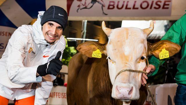 Julien Wanders pose avec un taureau après sa victoire. [Jean-Christophe Bott - Keystone]
