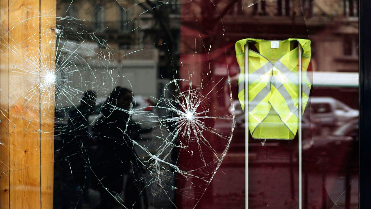 Une vitrine brisée affichant un gilet jaune, en soutien au mouvement de contestation. [Kamil Zihnioglu - AP Photo / Keystone]