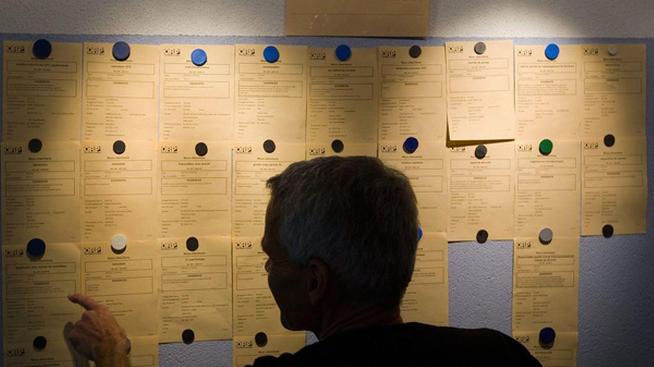 Une personne regarde les annonces d'emploi dans un office ORP. [Jean-Christophe Bott - Keystone]