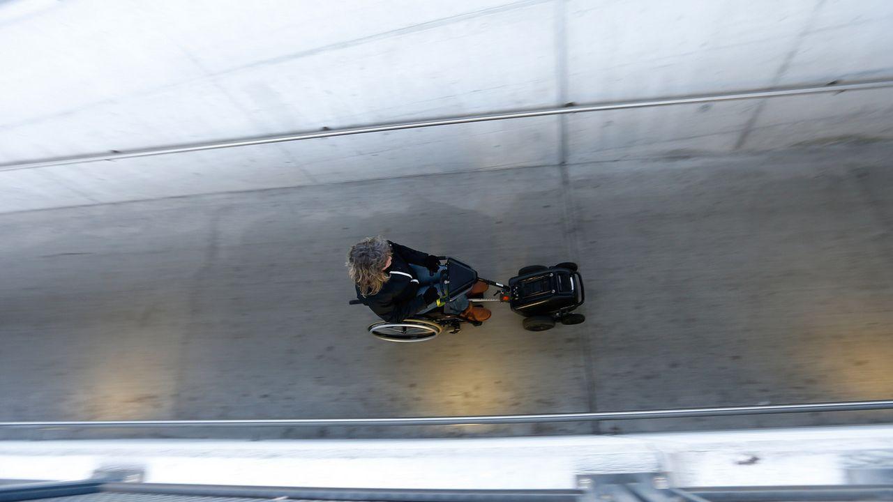 Une personne à mobilité réduite accède au quai d'une gare via une rampe. [Arno Balzarini - Keystone]