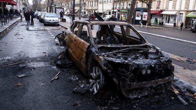 Une voiture incendiée sur les Champs-Elysées à Paris lors des manifestations des gilets jaunes. [EPA/Etienne Laurent - Keystone]