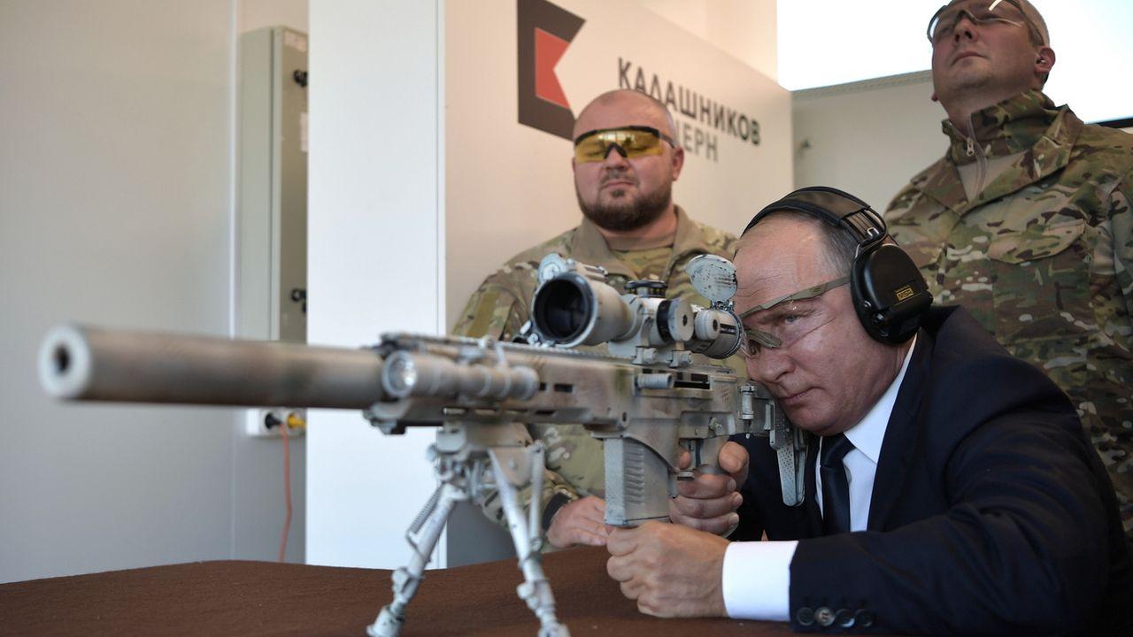 Le président russe Vladimir Poutine teste un fusil de tireur d'élite dans un parc d'attractions dédié à l'équipement militaire des troupes russes. [EPA/Sputnik/Kremlin Pool/Keystone]