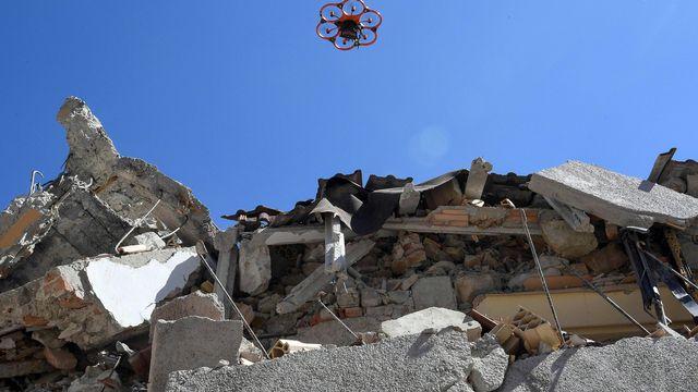 Un drone survole les débris d'une école en Italie après un séisme. [Alessandro Di Meo - ANSA via AP/Keystone]