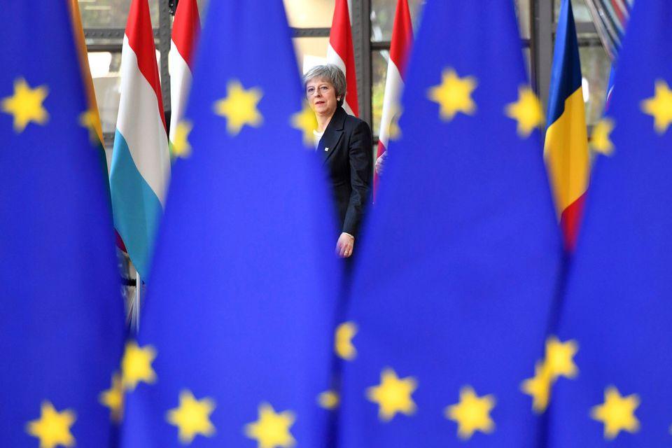 Jeudi 13 décembre: la Première ministre britannique Theresa May cachée derrière le drapeau européen. [AP Photo/Geert Vanden Wijngaert - Keystone]