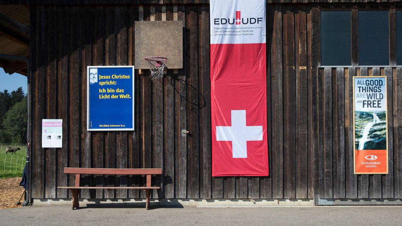 Un drapeau et des affiches lors d'une assemblée de délégués de l'UDF. [Peter Klaunzer - Keystone]