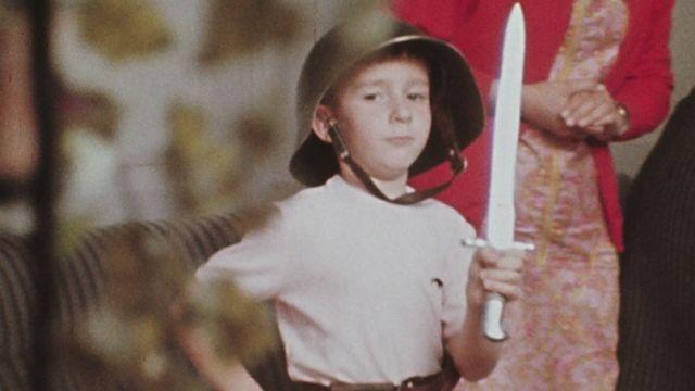 Petit Suisse jouant avec le matériel militaire de son milicien de père, 1969. [RTS]