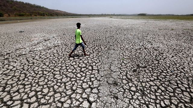 Un homme marche sur le lit d'un lac asséché en Inde (illustration). [Sanjeev Gupta - EPA/Keystone]