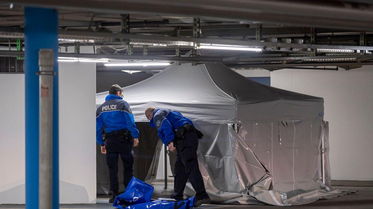 Des policiers genevois s'affairent sur les lieux où un jeune homme a été tué, dans le parking du centre commercial Planète Charmilles. [Martial Trezzini - KEYSTONE]