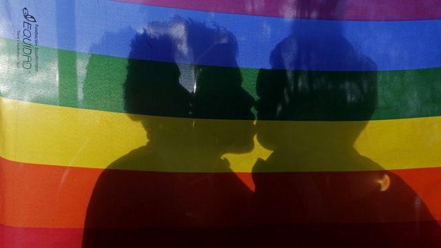 Un couple d'homosexuels s'embrase derrière un drapeau aux couleurs arc en ciel. [Dolores Ochoa - AP/Keystone]