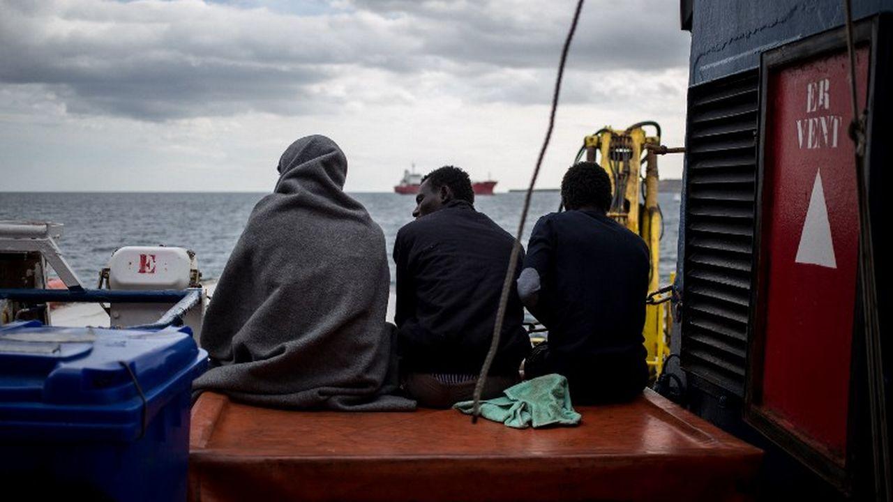 Trois migrants à bord du navire de sauvetage Sea Watch 3, battant pavillon néerlandais. [Federico Scoppa - AFP]