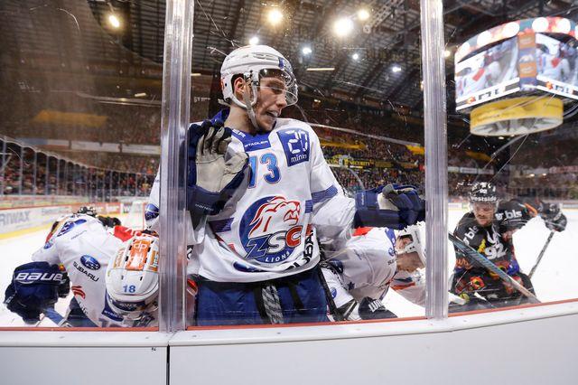 Le Zurichois Mike Kuenzle lutte à la bande sur la glace du CP Berne. [Peter Klaunzer - Keystone]