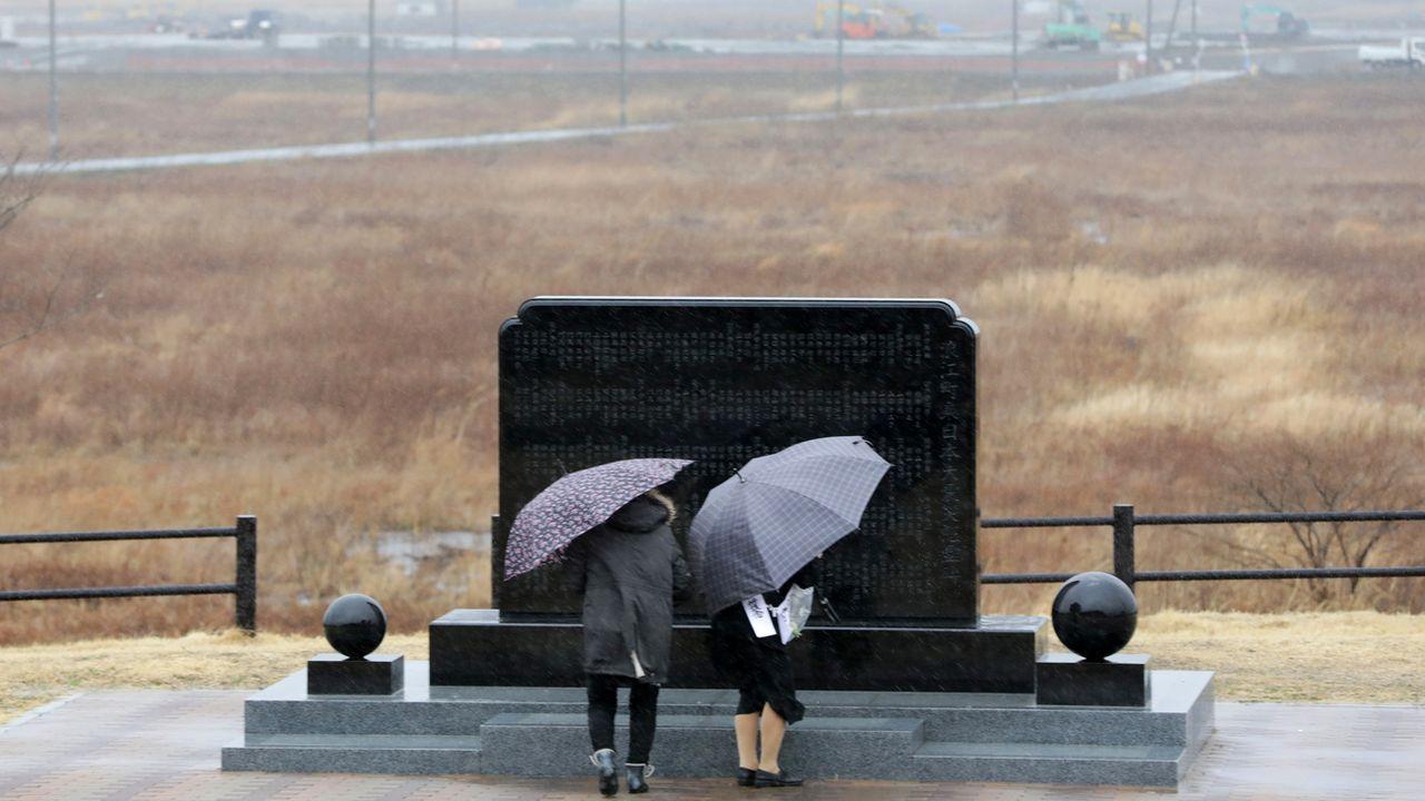 Deux personnes prient devant le mémorial de Fukushima, huit ans après le séisme meurtrier. [EPA/Jiji Press Japan - Keystone]