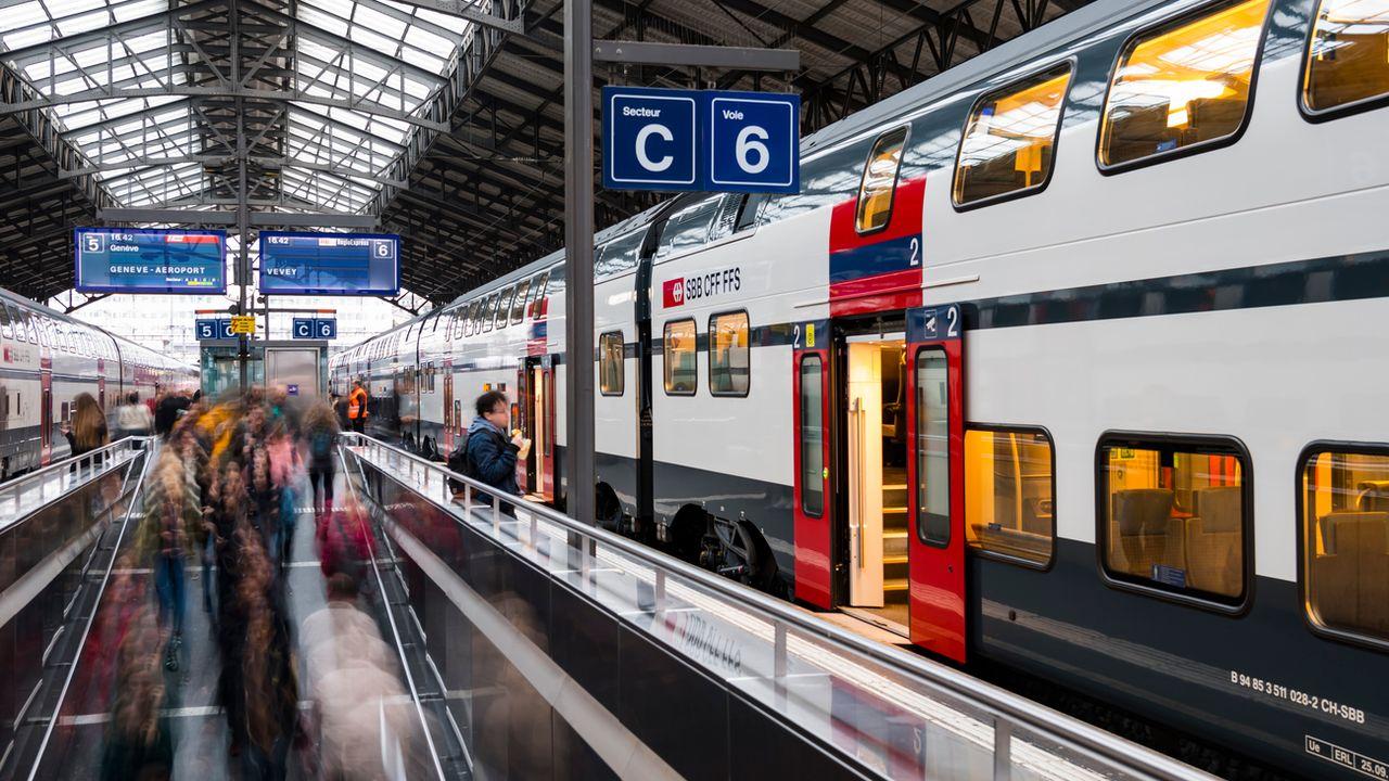 Des voyageurs et des pendulaires circulent sur un quai devant un train CFF SBB le 14 novembre 2018 dans la gare de Lausanne. [Jean-Christophe Bott - Keystone]