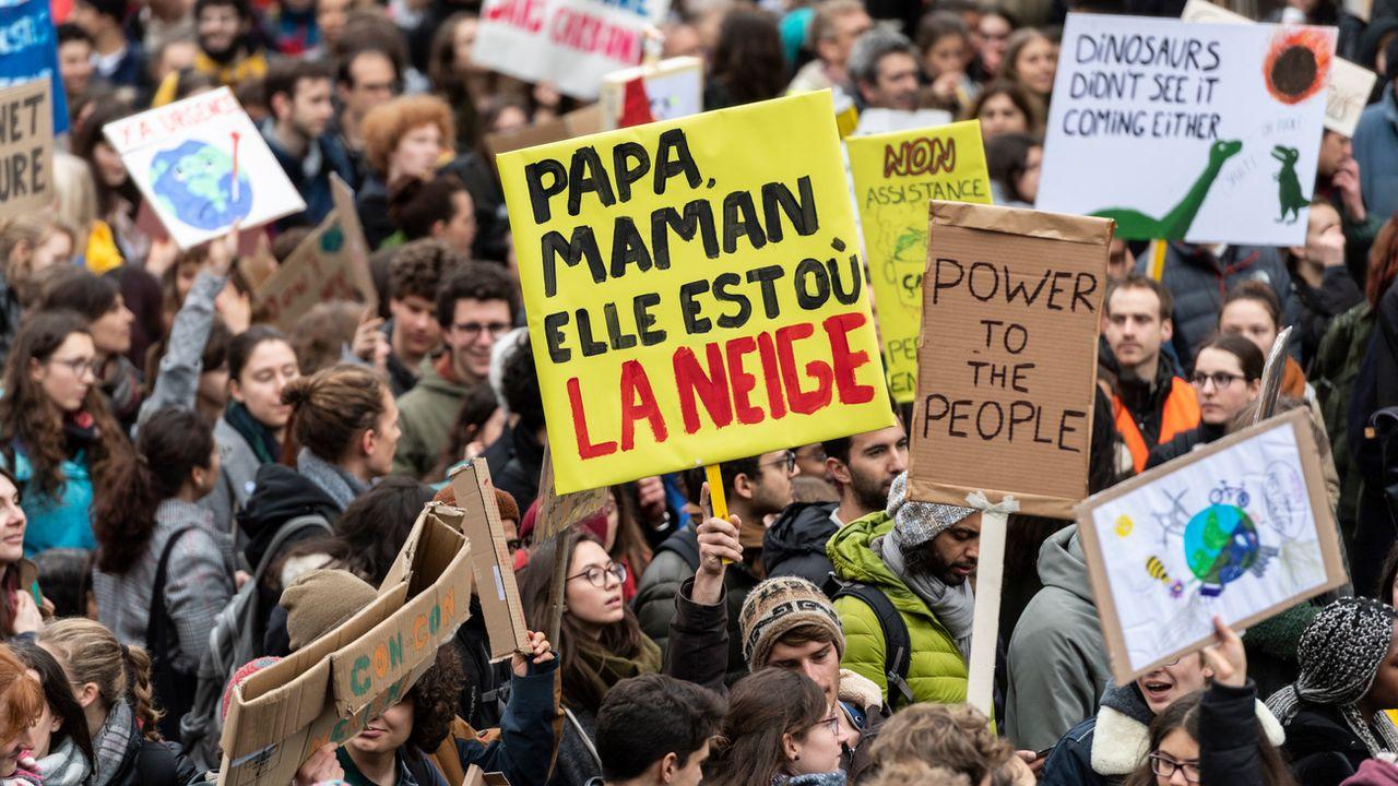 Un manifestant lausannois esquisse un futur inquiétant sur sa pancarte. [Jean-Christophe Bott - KEYSTONE]