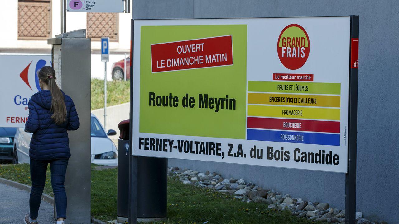 Un panneau publicitaire à Genève vantant l'ouverture le dimanche d'un magasin français. [Salvatore Di Nolfi - Keystone]