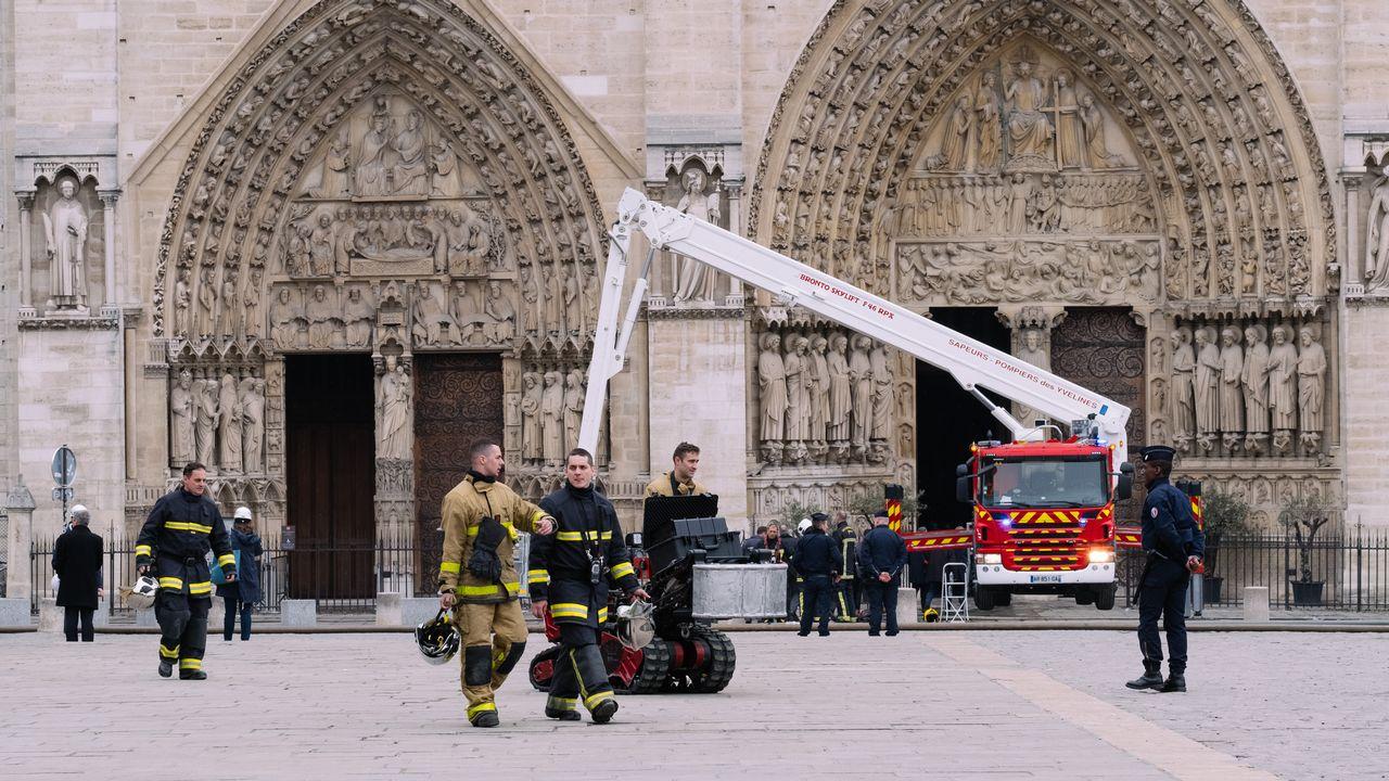 Le parvis de Notre-Dame, où des pompiers finissent de s'affairer après l'incendie qui a ravagé la cathédrale le 16 avril 2019. [Marie Magnin / Hans Lucas - AFP]