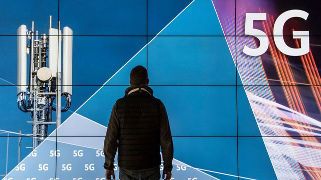 Un homme se tient devant un écran affichant une antenne 5G. [Boris Roessler - Keystone]
