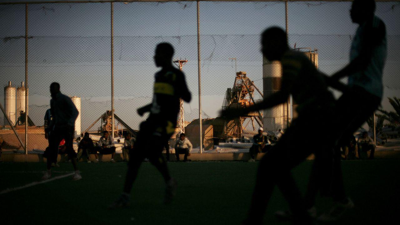 Des jeunes hommes jouent au football dans un camps de réfugiés en Libye. [Manu Brabo - AP-Keystone]