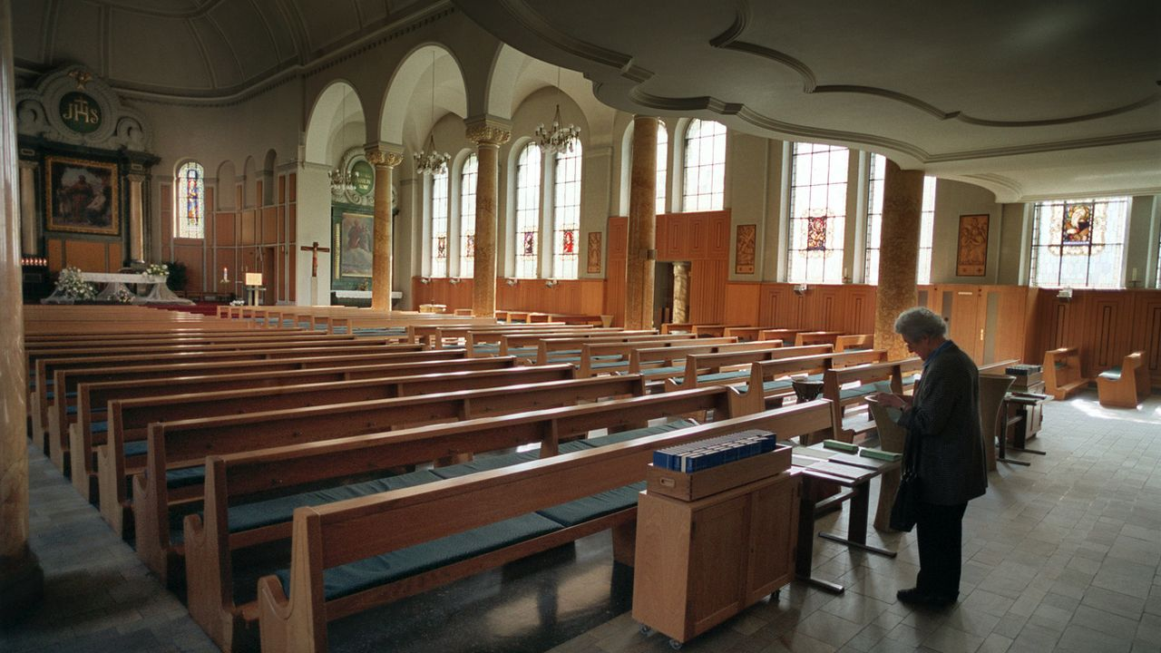 Une femme dans une église catholique à Zurich. [Gaetan Bally - Keystone]