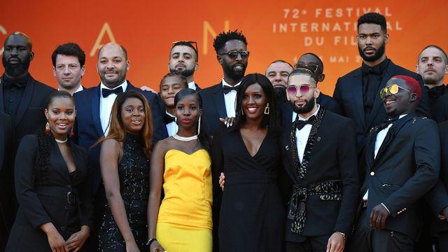 """Le réalisateur Ladj Ly (au centre) pose avec son équipe lors de la présentation de son film """"Les Misérables"""" à la 72e édition du Festival de Cannes. [Alberto Pizzoli - AFP]"""