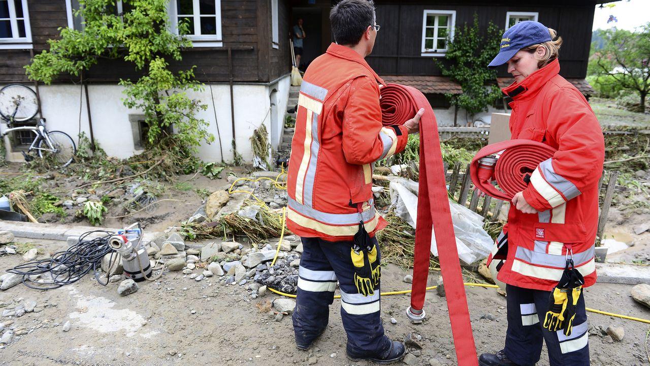 Deux pompiers sur les lieux d'une inondation à Dierikon (LU). [Urs Flueeler - Keystone]