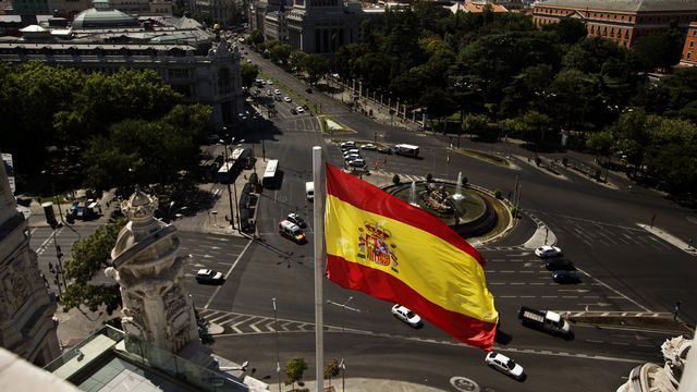 Le drapeau espagnol flotte à Madrid. [AP Photo/Daniel Ochoa de Olza - Keystone]