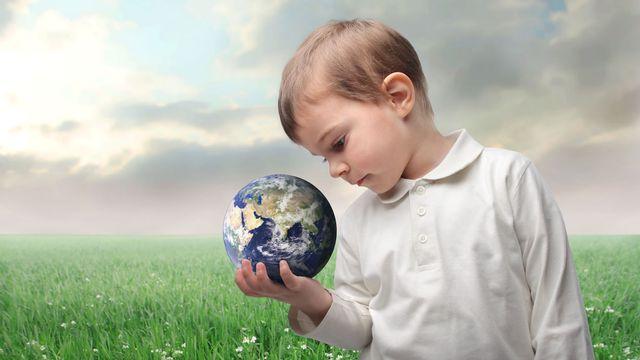 Un enfant regarde la terre qu'il tient dans sa main. [olly18 - Depositphotos]