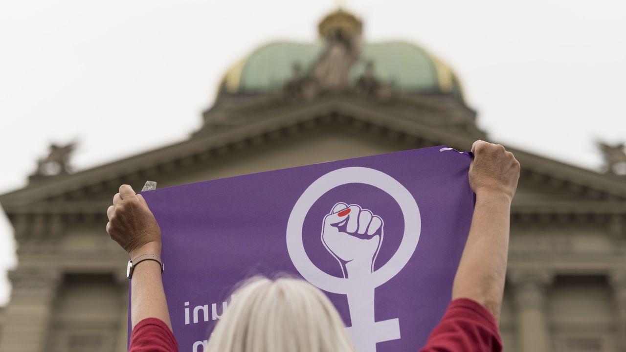 Une femme portant un drapeau de la grève devant le Palais fédéral, ce 14 juin 2019. [Alessandro della Valle - keystone]