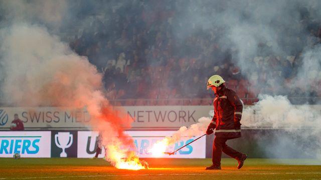 Un pompier intervient pour se saisir d'un engin pyrotechnique lors d'un match entre Sion et Grasshopper. [Salvatore Di Nolfi - Keystone]