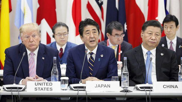Donald Trump et Xi Jinping entourent le premier ministre japonais Shinzo Abe lors du discours d'ouverture du G20. [Keystone/EPA]