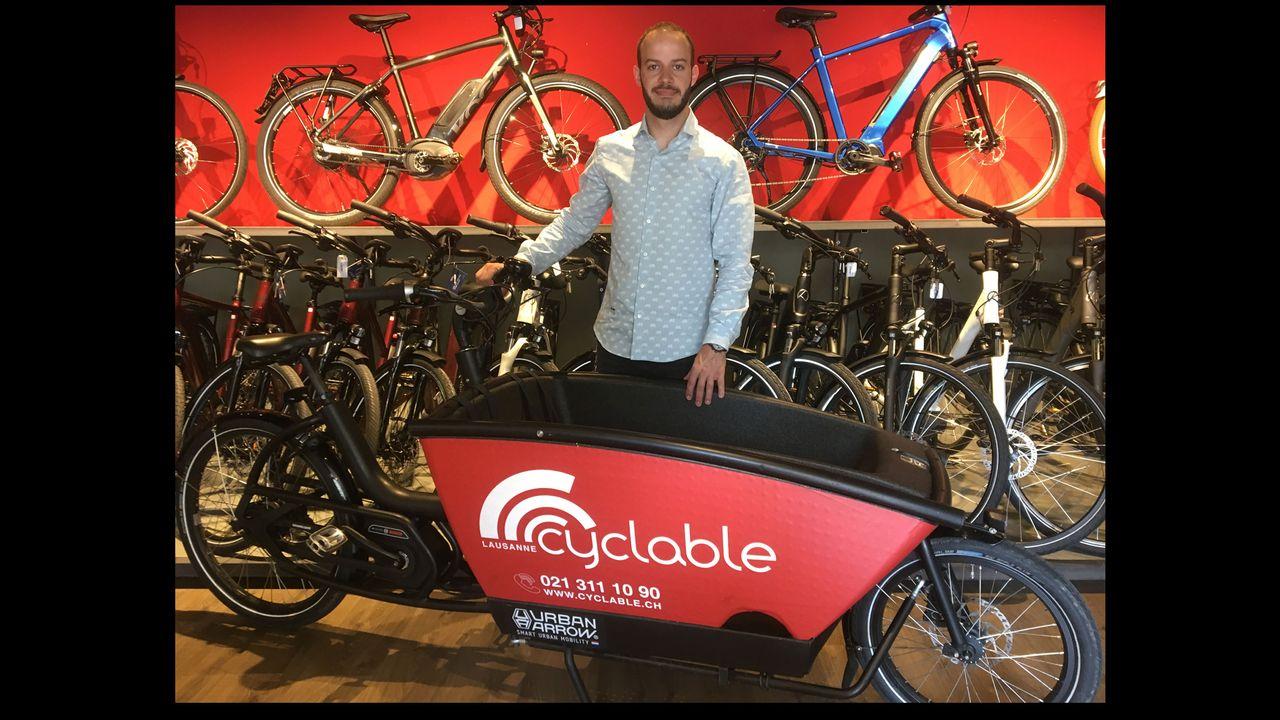 Romain Marandet, patron de la boutique Cyclable, aux côtés d'un modèle de vélo cargo électrique. [Jérôme Zimmermann - RTS]