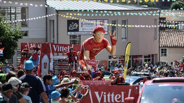 Des spectateurs regardent La Caravane publicitaire du Tour de France.  [Jeff PACHOUD - AFP]