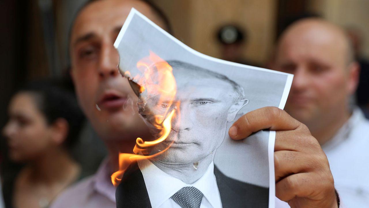 Un protestataire brûle une image du président russe lors d'une manifestation à Tbilissi le 20.06.2019. [Irakli Gedenidze - Reuters]