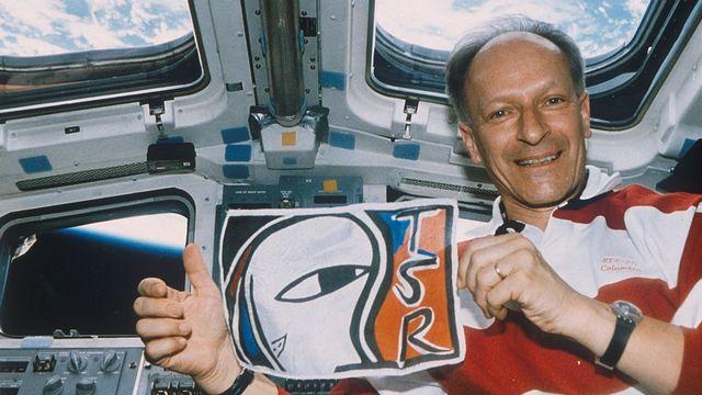 Claude Nicollier arbore le logo de la TSR depuis la navette spatiale Columbia, 1996.
