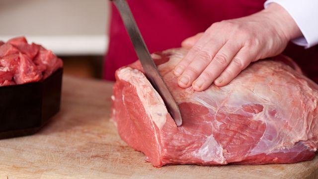 un boucher coupe la viande crue. [DepositPhotos]