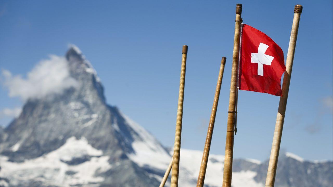 Un drapeau suisse et des cors des Alpes photographiés près de Zermatt. [Valentin Flauraud - Keystone]