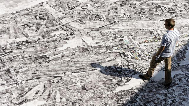 Une personne observe un collage géant d'images du photographe japonais Sohei Nishino représentant la ville de Berne. Vevey, festival Images 2012.  [Laurent Gillieron - Keystone]