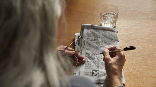Une femme âgée faisant un jeu de chiffres. [Christof Schuerpf - Keystone]