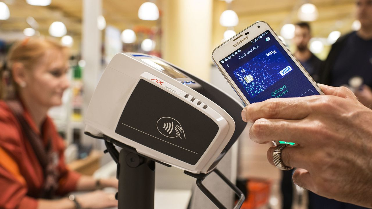 Le paiement sans contact peut se faire à l'aide d'un smartphone ou d'une carte de débit. [Christian Beutler - Keystone]