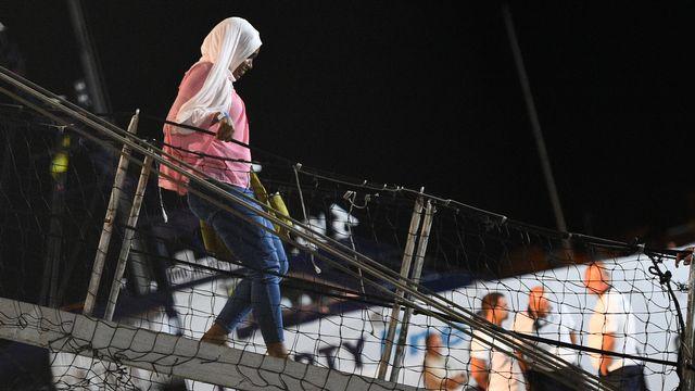 Une migrante débarque de l'Open Arms au port de Lampedusa après une décision de la justice italienne. [Guglielmo Mangiapane - Reuters]